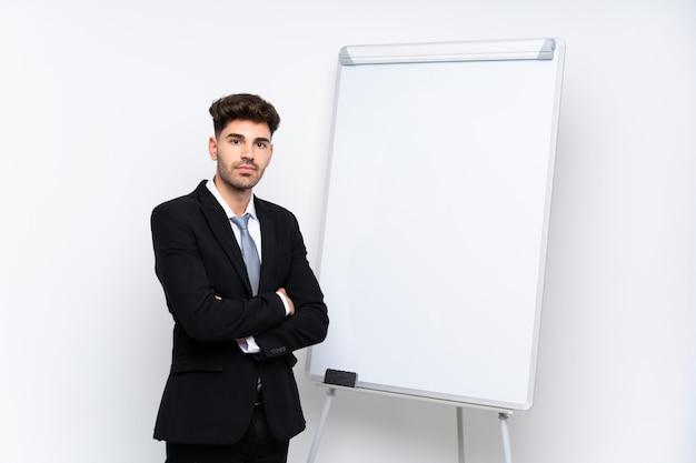 ホワイトボードにプレゼンテーションをしながら腕を組んでホワイトボードにプレゼンテーションを行う青年実業家