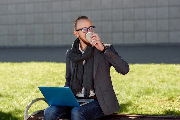 Young businessman in glasses dressed in jacket with scarf drinks coffee and using laptop on a lunch break outdoors sitting on the wooden bench in the park near business centre.