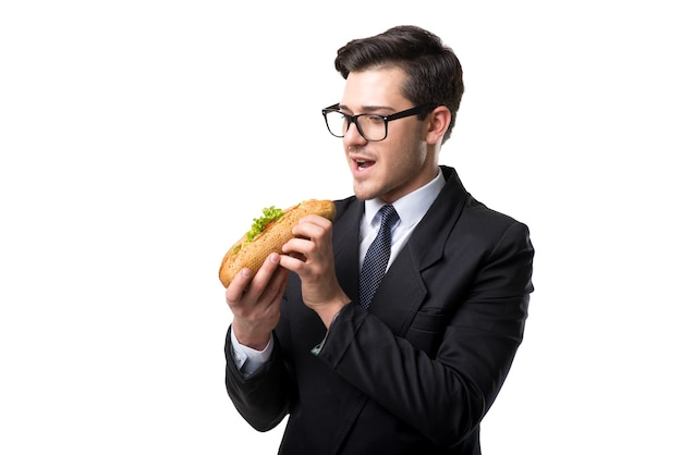 Young businessman in glasses, tie and black suit eats burger, isolated on white