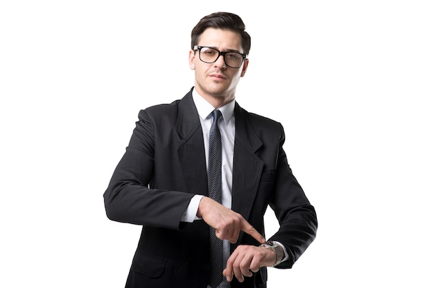 Young businessman in glasses, tie and black suit point a finger on the watch, isolated on white