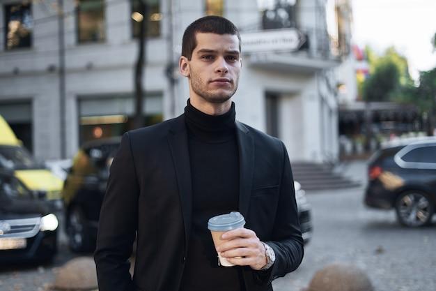 Giovane uomo d'affari che va al lavoro con caffè