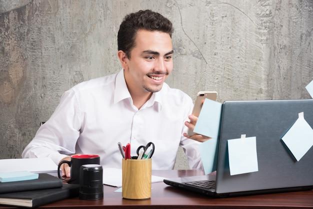 젊은 사업가 사무실 책상에서 행복 소식을 얻었다.