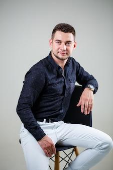 Молодой бизнесмен парень в черной рубашке и белых брюках на белом фоне