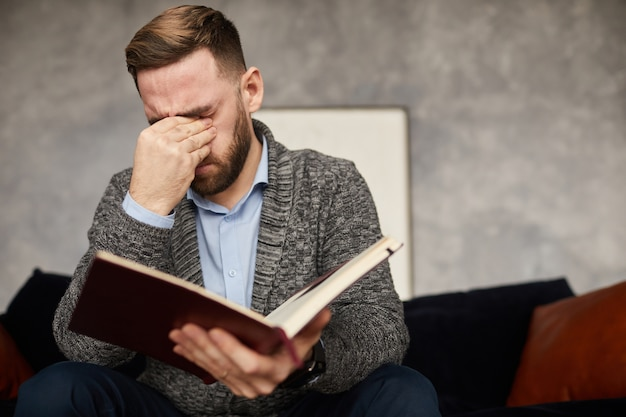 Young businessman has a headache he sitting on sofa with notepad and tired of work