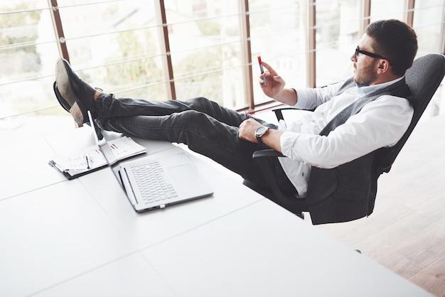 젊은 사업가 의자에 앉아있는 동안 휴식을 가지고 클린 룸의 테이블에 다리를 넣어