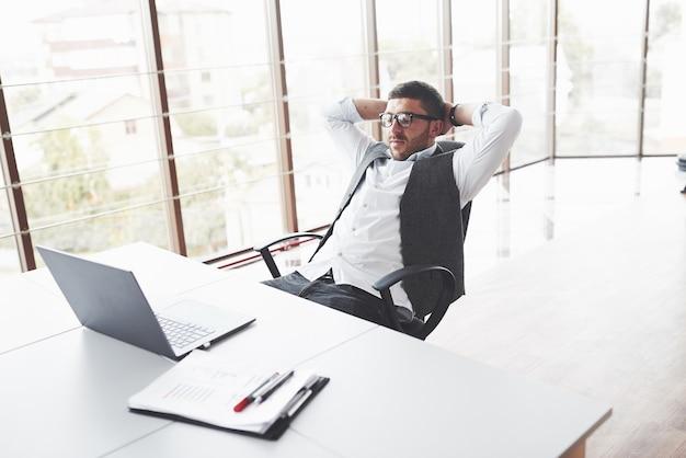 クリーンルームの椅子に座って休憩し、目を閉じている青年実業家