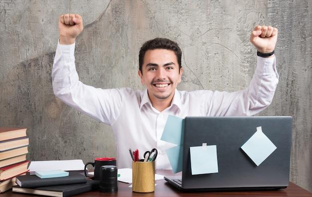 사무실 책상에서 최고의 순간을 보내고 젊은 사업가.