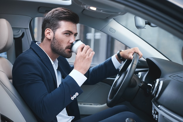 Young businessman having a coffee in his car