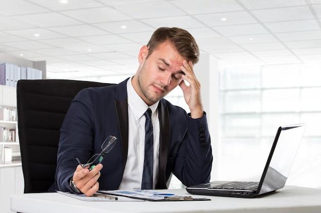 Молодой бизнесмен с головной болью, подчеркнул с его работой