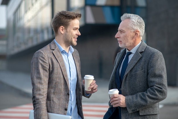 Young businessman and his boss discussing project while having coffee