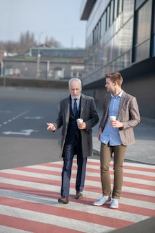 Young businessman and his mature mentor crossing the street having a break at work