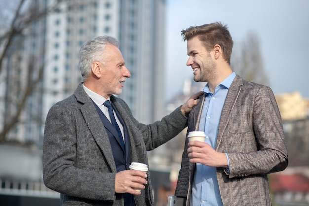 Young businessman and his mature mentor smiling while having a conversation