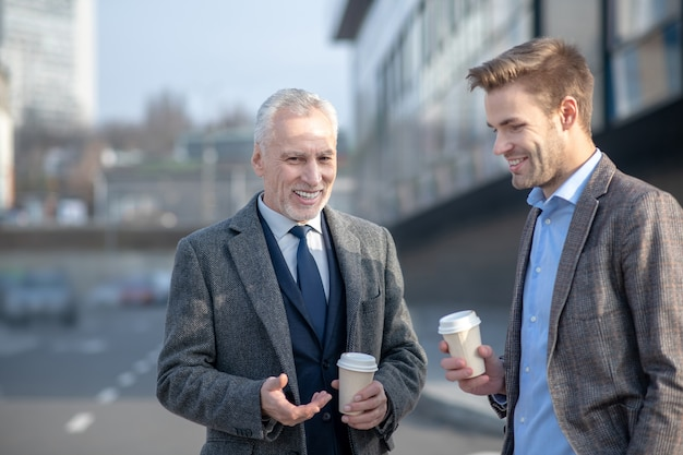 Young businessman and his mature mentor talking in the street having a break at work