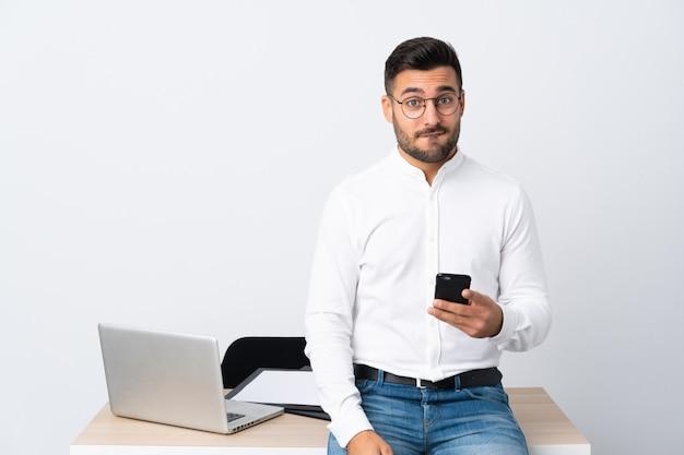 疑問を持つと混乱の表情を持つ携帯電話を保持している青年実業家