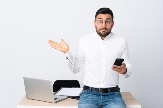 混乱の表情を持つ携帯電話を保持している青年実業家