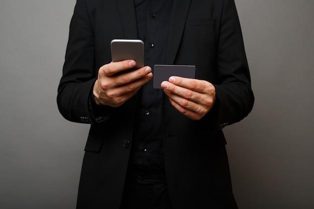Молодой бизнесмен держит телефон и кредитную карту