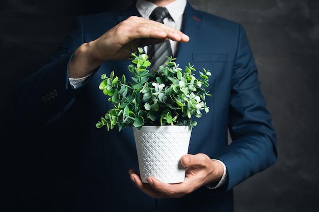 어두운 표면에 식물 꽃병을 들고 젊은 사업가