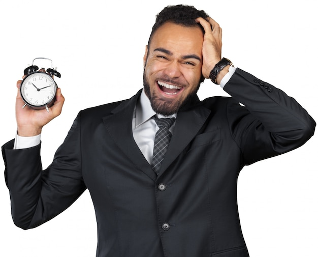 Young businessman holding alarm clock isolated
