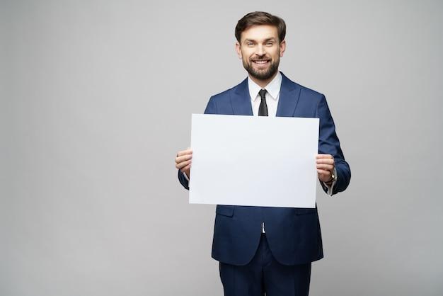 灰色の壁に空白記号を保持している青年実業家