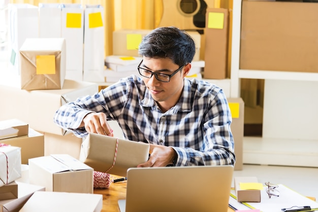 Young businessman holding a cardboard shipping from online shopping.businessman receiving parcel in