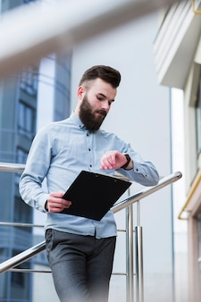 Young businessman holding clipboard in hand checking time