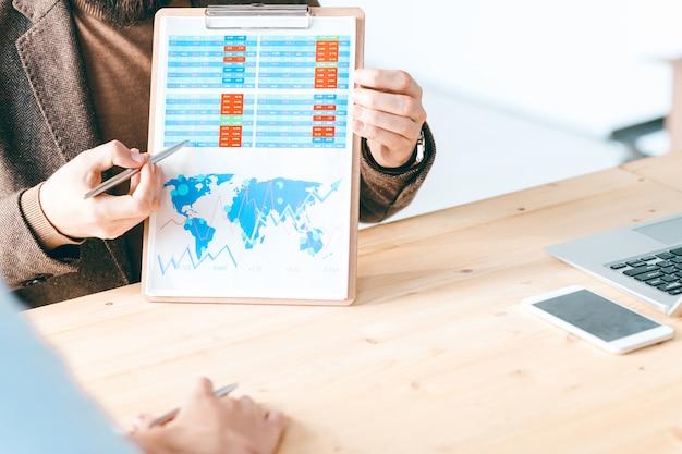 재무 문서와 클립 보드를 들고 회의에서 동료에게 데이터를 설명하는 동안 차트를 가리키는 젊은 사업가