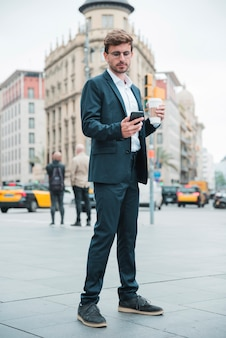 Young businessman holding coffee cup standing on street looking at mobile phone