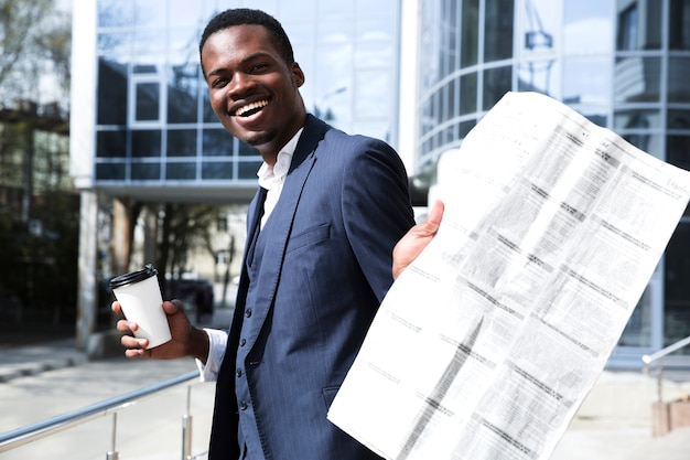 Young businessman holding disposable coffee cup showing newspaper toward camera