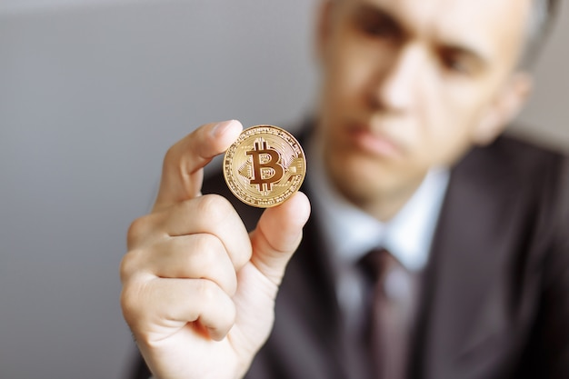 Young businessman holding in hand symbol of bitcoin crypto currency