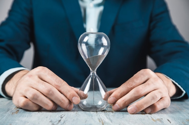Young businessman holding hourglass in his hand