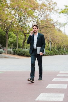 Young businessman holding laptop in hand talking on mobile phone walking on road