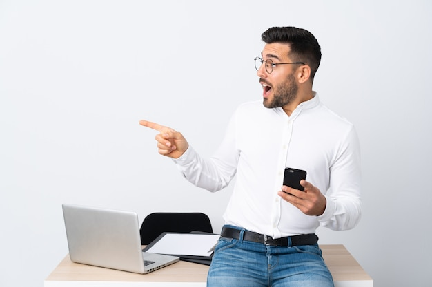 Young businessman holding a mobile phone pointing finger to the side