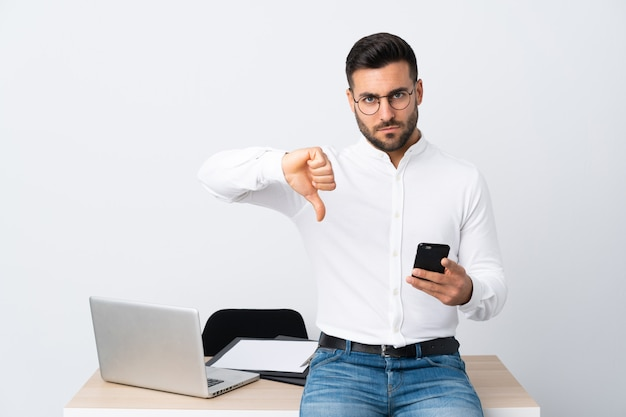 Young businessman holding a mobile phone showing thumb down sign