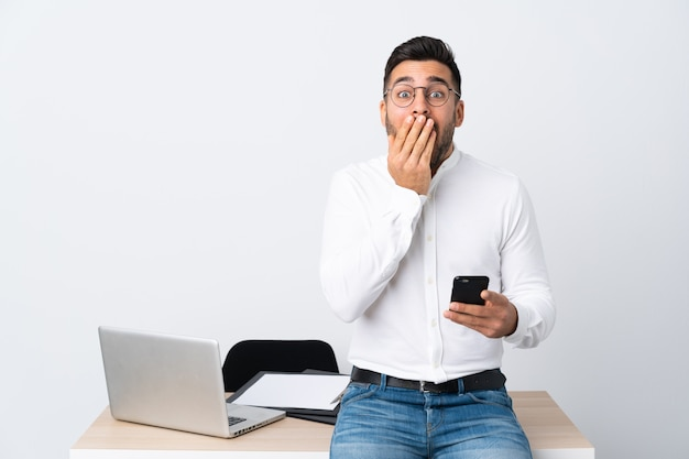 Young businessman holding a mobile phone with surprise facial expression