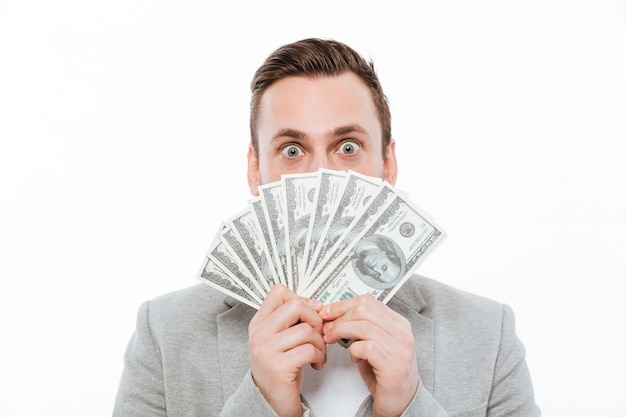 Young businessman holding money covering face.