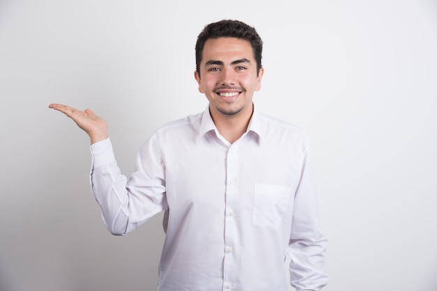 Young businessman holding open space on white background.
