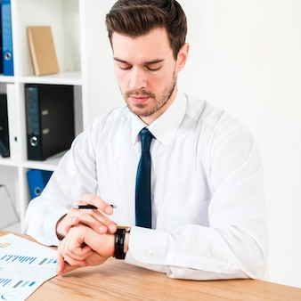Young businessman holding pen in hand watching the time on wrist watch