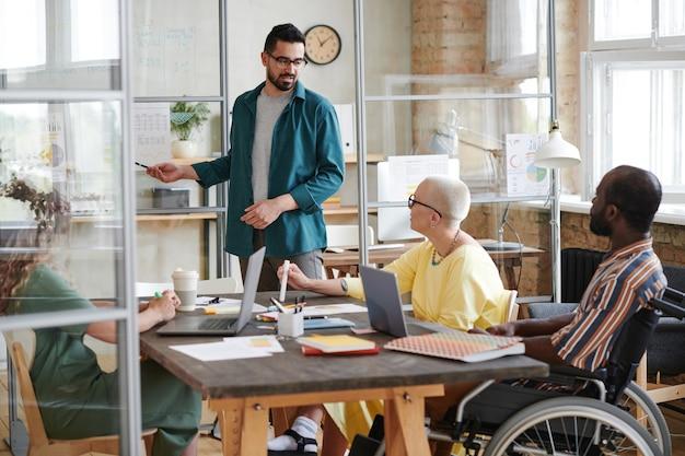 Молодой бизнесмен, проводящий презентацию для своих коллег во время встречи в зале заседаний, они планируют совместную работу