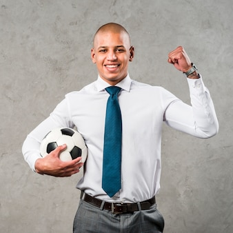 Young businessman holding soccer ball in hand clenching her fist standing against grey wall
