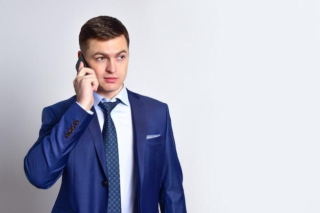 Молодой бизнесмен в синем костюме и галстуке разговаривает по смартфону
