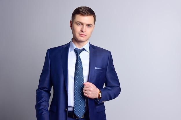 클래식 블루 양복과 넥타이에 젊은 사업가 자신있게 카메라에 보인다