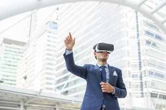 Young businessman in black suit wearing virtual reality goggles.