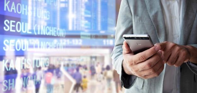 Молодой бизнесмен в синем костюме с помощью мобильного приложения для бронирования авиабилетов