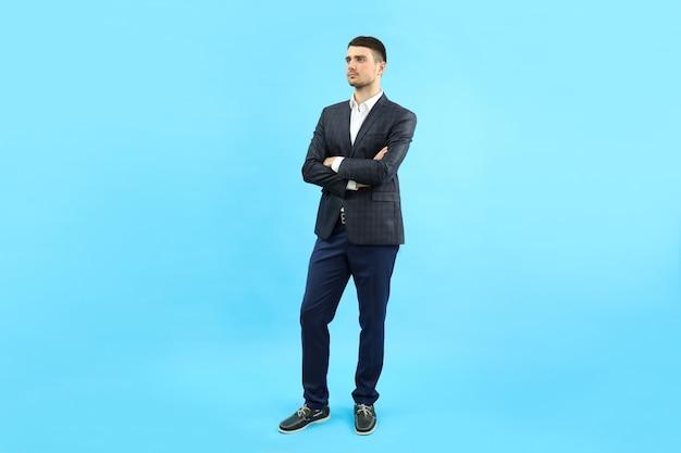 Молодой бизнесмен в классическом костюме на синем фоне.