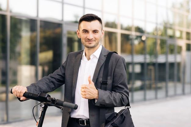 Молодой бизнесмен в элегантном костюме, стоя на открытом воздухе, весело улыбаясь и показывая большой палец вверх красивого