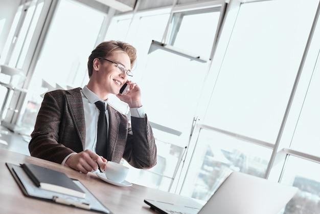 Молодой предприниматель в очках в офисе, сидя пить кофе