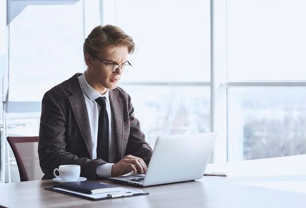 Молодой предприниматель в очках в офисе, сидя на коленях