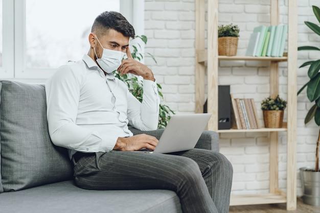 Молодой бизнесмен в маске для лица, сидя на диване и используя ноутбук дома