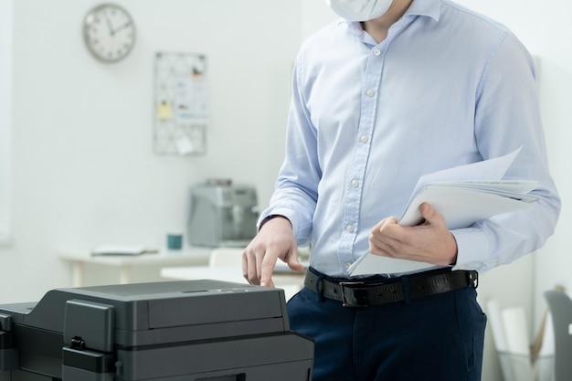 Молодой бизнесмен в строгой одежде и защитной маске держит стопку бумаг, стоя у ксерокопии и нажимая кнопку пуска