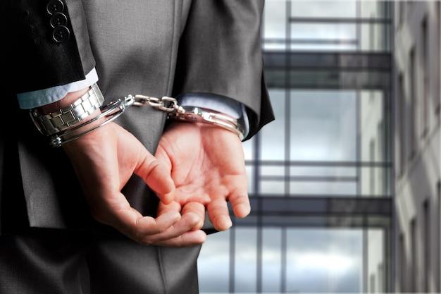 Молодой бизнесмен в наручниках на фоне диффузного суда